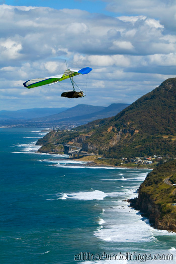 The Sea Cliff Bridge in the centre of the shot, just below the hang glider